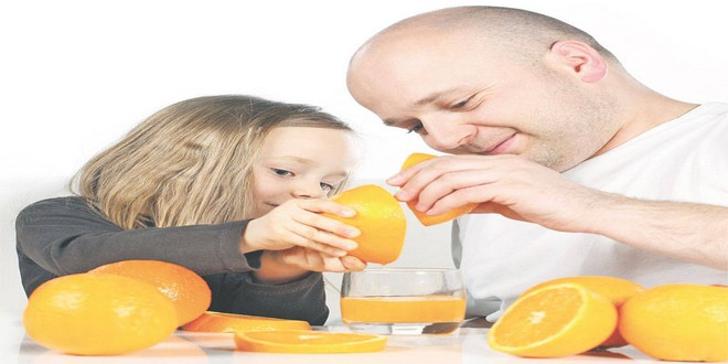Wiki Juices - Father and daughter making orange juice